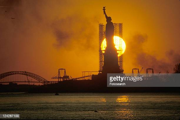 Silhouetted Statue of Liberty with scaffolding at sunset, New York City, New York