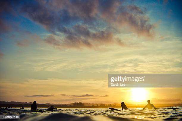 Silhouetted surfers at sunset