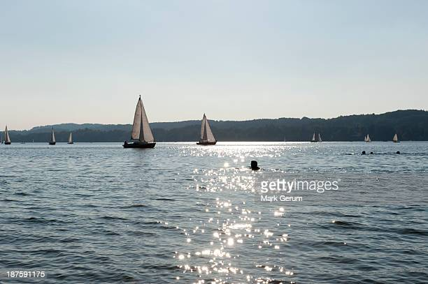 silhouetted swimmers and sailboats in lake at starnberger sea, bavaria, germany - starnberg photos et images de collection