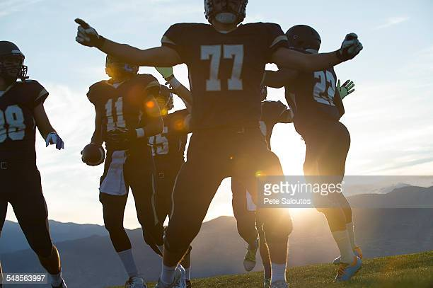 Silhouetted teenage and young male american football team celebrating at sunset