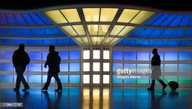 silhouetted travelers moving through a colorful walkway in chicago o'hare international airport - road warrior stock photos and pictures