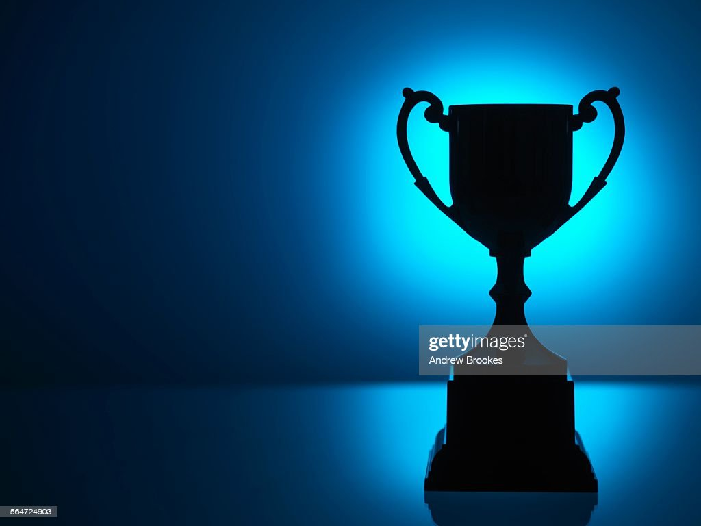 Silhouetted trophy with blue background : Foto de stock