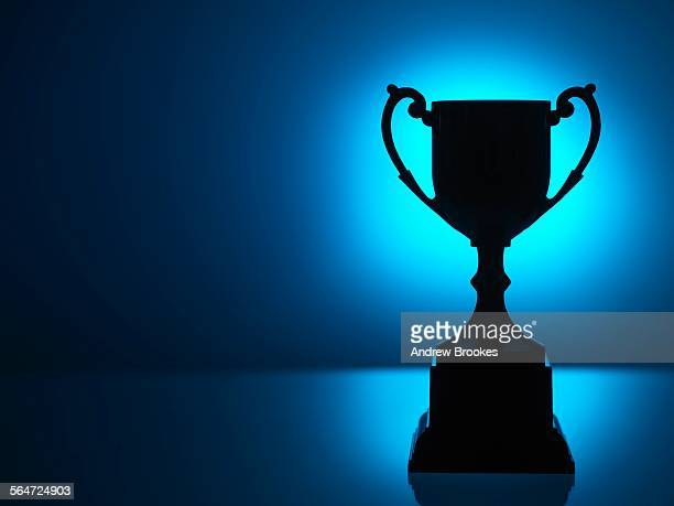 silhouetted trophy with blue background - trofeo fotografías e imágenes de stock