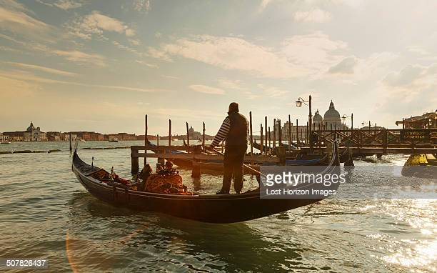 silhouetted view of gondolier at sunset, venice, veneto, italy - gondola traditional boat stock pictures, royalty-free photos & images