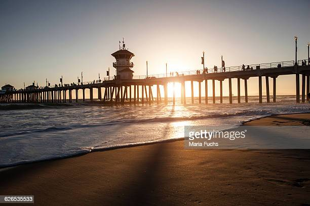 silhouetted view of pier at sunset, huntington beach, california, usa - huntington beach stock pictures, royalty-free photos & images