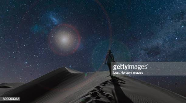 silhouetted view of woman on dunes under starry night sky, namib desert, namibia - deserto da namíbia - fotografias e filmes do acervo