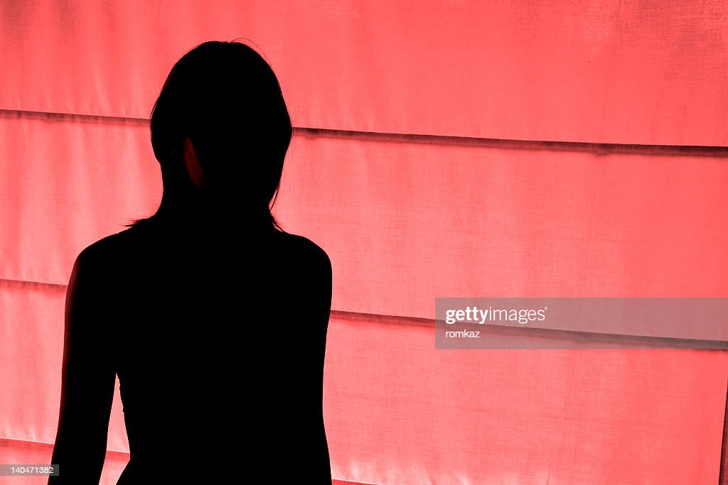 Silhouetted view of woman standing at red light district