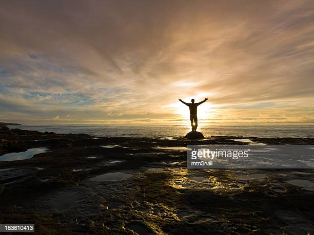 Silhouetted with arms raised on rocky beach at sunrise