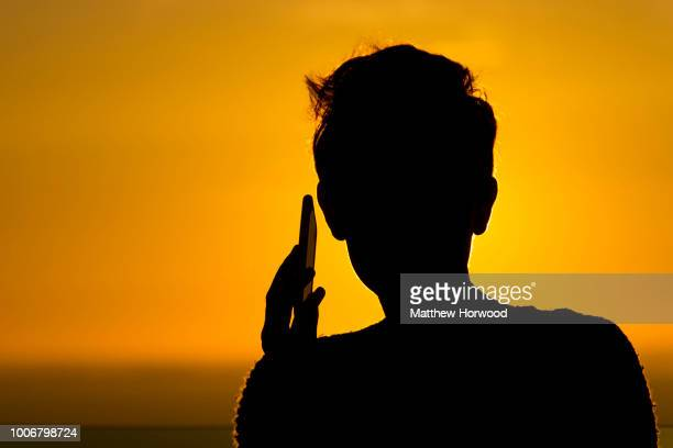 Silhouetted woman holds a mobile phone to her ear during sunset on October 23, 2014 in Cardiff, United Kingdom.