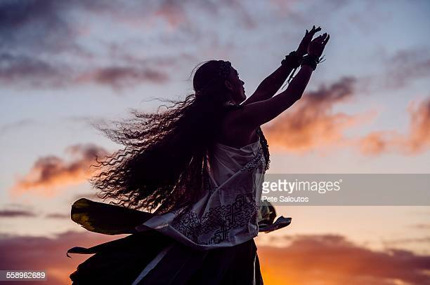 Silhouetted woman hula dancing wearing traditional costume at dusk, Maui, Hawaii, USA