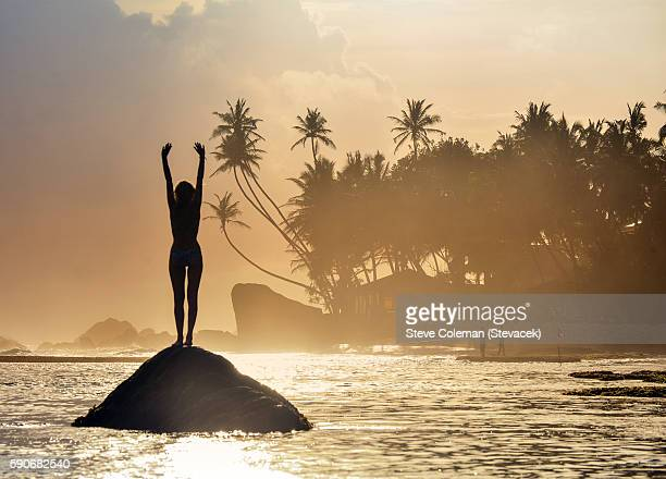 Silhouetted woman on a tropical beach at dusk