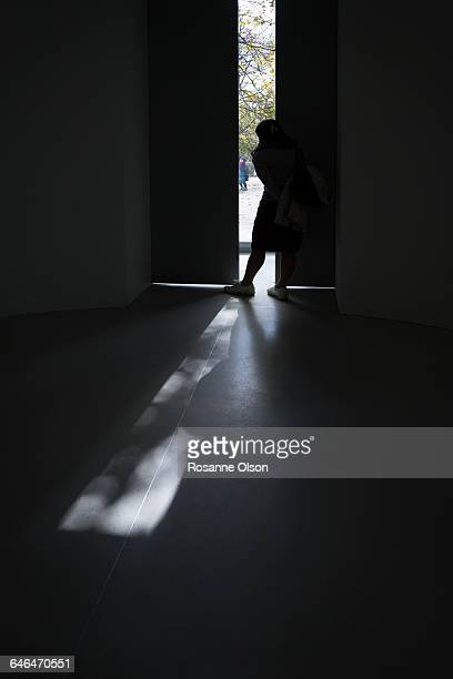 A silhouetted woman peers out an open door.