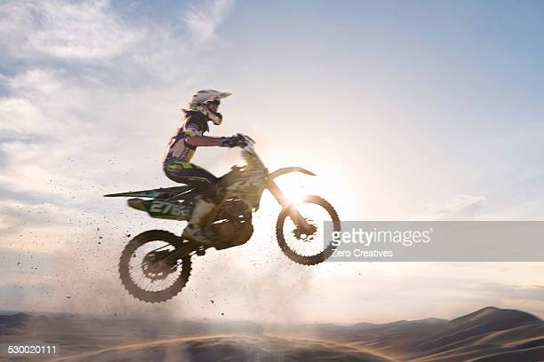 silhouetted young male motocross racer jumping over mud track - motocross fotografías e imágenes de stock