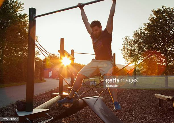 Silhouetted young man swinging on playground climbing frame at sunset