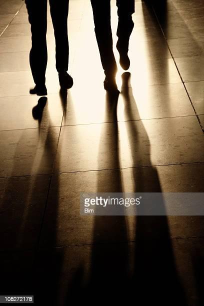 Silhouettes et les ombres de deux Homme d'affaires marchant dans le couloir