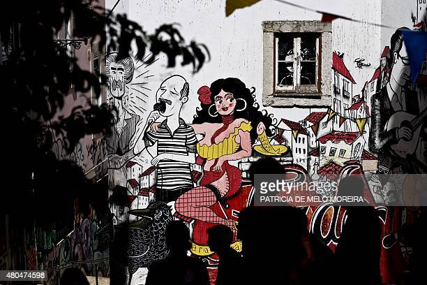Silhouettes are pictured in front of a graffiti representing the history of Portuguese best known music genre the Fado at Sao Cristovao stairs in...