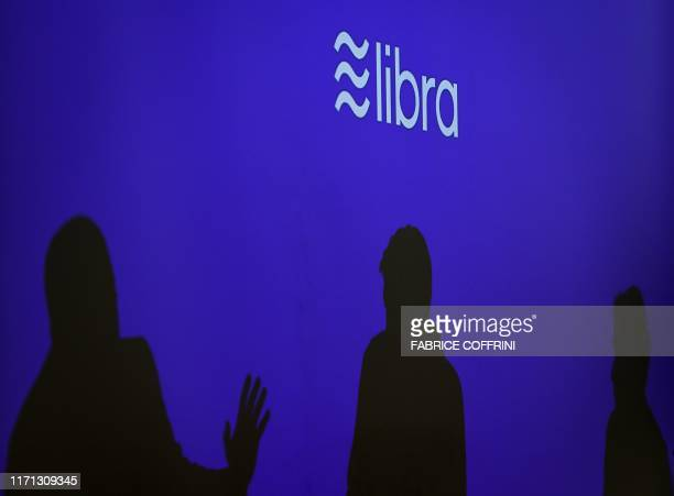 Silhouettes are seen beneath a sign of Libra the cryptocurrency project launched by Facebook during a conference at marketing and communication...