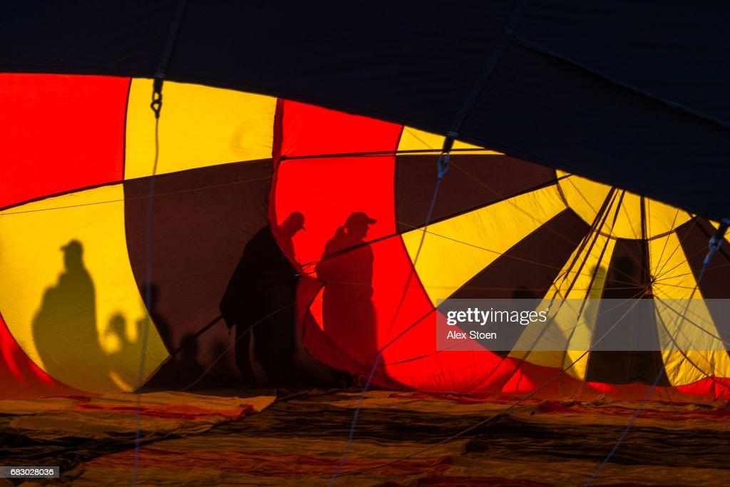 Silhouettes behind a hot air ballon : Stock Photo