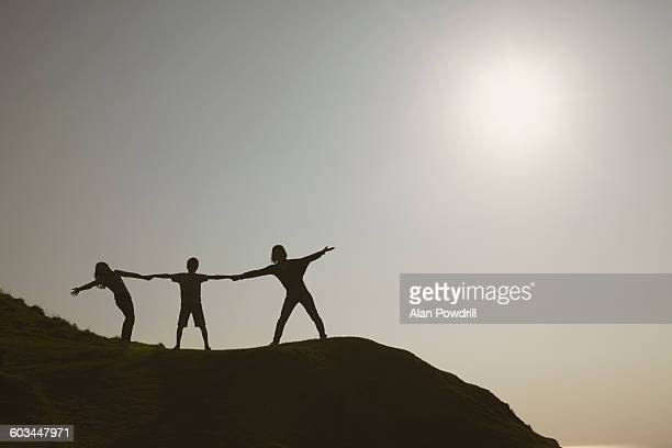 3 silhouettes holding hands on a hill