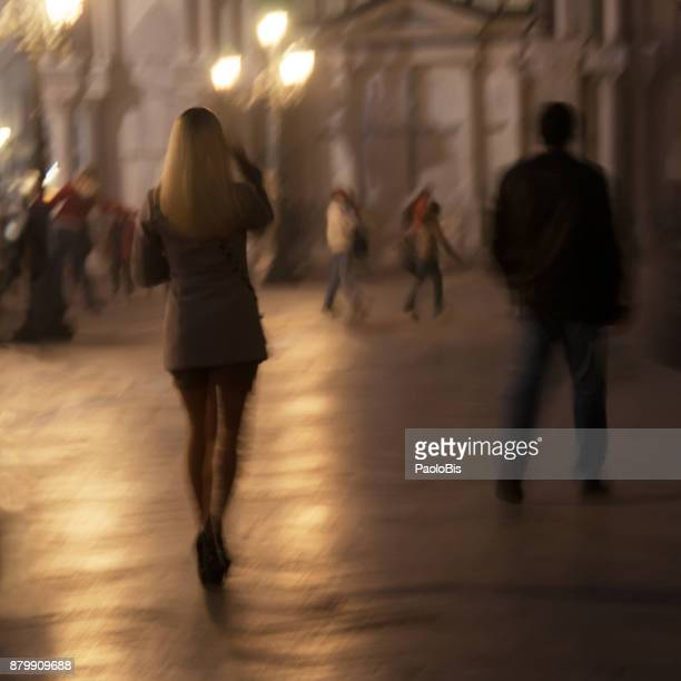 Silhouettes of a blond woman walking in the night, Venice