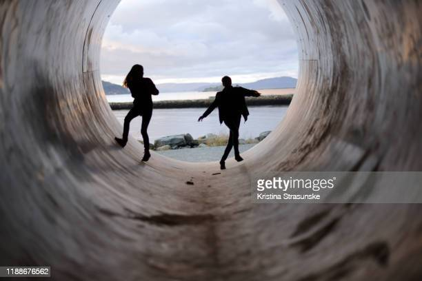 silhouettes of a boy and a girl in a tunnel - kristina strasunske stock pictures, royalty-free photos & images