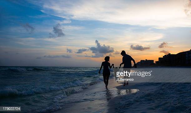 Silhouettes of a couple and child on a beautiful beach