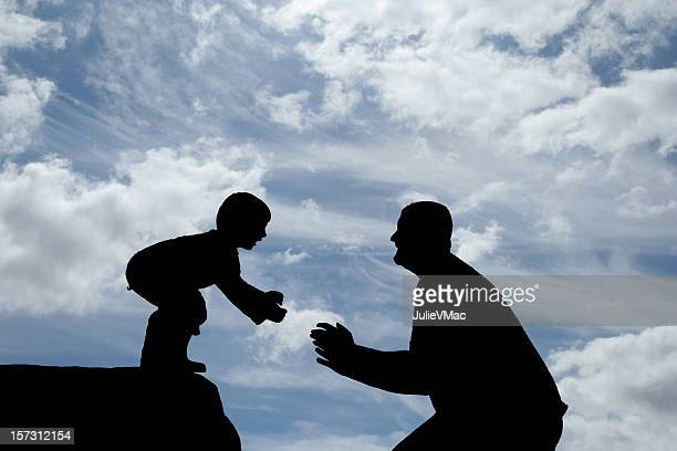 silhouettes of a father and son playing - leap of faith stock photos and pictures