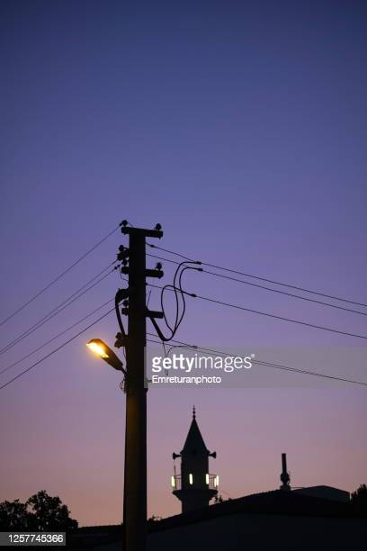 silhouettes of a lamp post and minater at sunset,cesme.close up of silhouettes of an street lamp and minaret of a mosque at sunset in dalyankoy,cesme. - emreturanphoto stock pictures, royalty-free photos & images