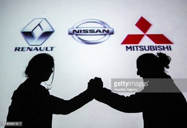 Silhouettes of a man and a woman are seen in front of the logos of Renault, Nissan and Mitsubishi, in Ankara, Turkey on November 30, 2019.