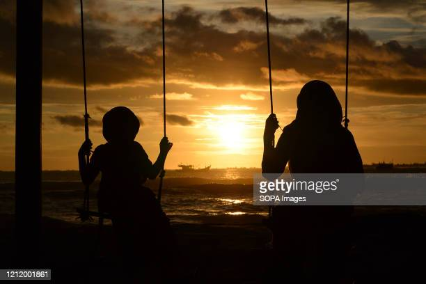 Silhouettes of a mother and child on a swing watching the sunset at Susoh beach.