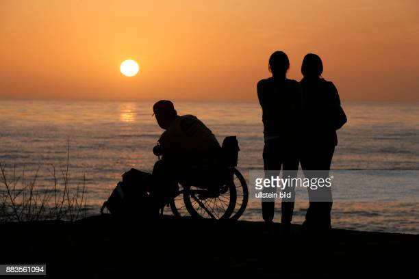 Silhouettes of a wheelchair user and a couple stand out against sunset at Sunset Cliffs Boulevard in Ocean Beach