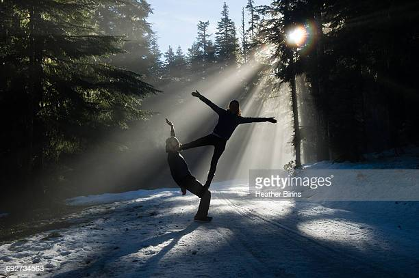 Silhouettes of acrobats in snow covered forest balancing, Frog lake, Mount Hood, Oregon, USA