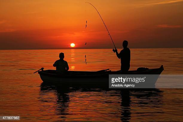 Silhouettes of amateur fishermen are seen during sunset in Abana district of Kastamonu a province in the Black Sea region of Turkey on June 13 2015