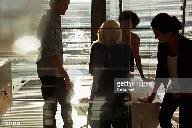 Silhouettes of business people meeting in conference room