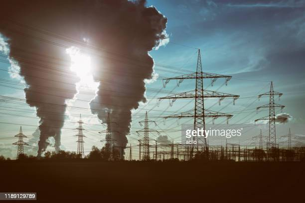 silhouettes of electricity pylons and two power plants with pollution - greenhouse gas stock pictures, royalty-free photos & images