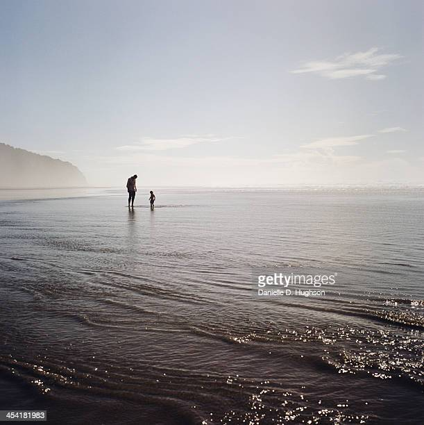 silhouettes of father and child at beach - mid distance stock pictures, royalty-free photos & images