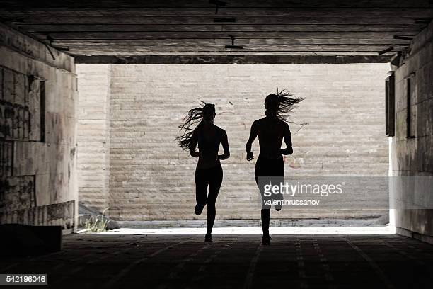 Silhouettes of female athletes running in underpass