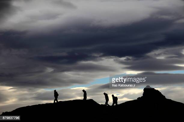 Silhouettes of four hikers against dramatic sky in Iceland