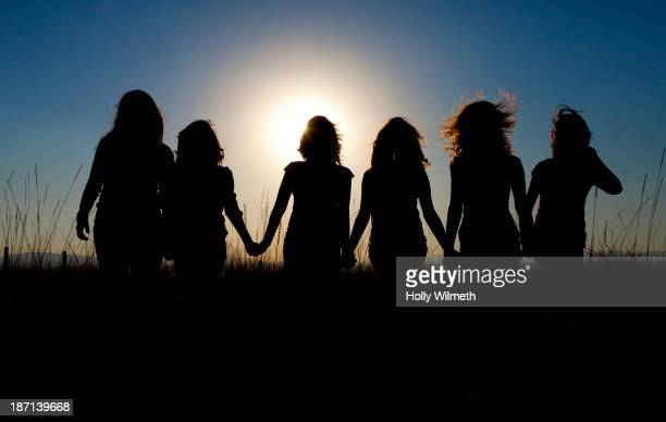 Silhouettes of girls walking in tall grass