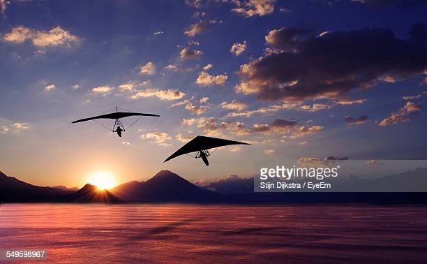 Silhouettes Of Hang Gliders Above Lake At Sunset