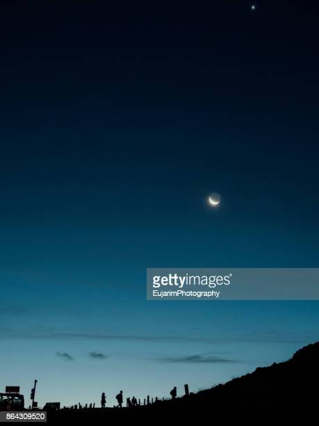 silhouettes of hikers at dawn with the moon and the morning star in the sky - luna nera foto e immagini stock