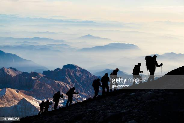 silhouettes of hikers at dusk - mountain peak stock pictures, royalty-free photos & images