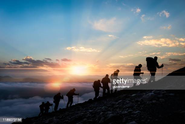 silhouettes of hikers at sunset - sports team stock pictures, royalty-free photos & images
