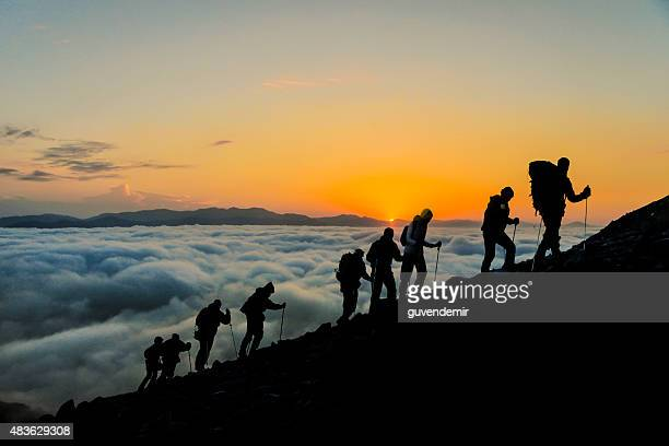 silhouettes of hikers at sunset - mountain peak stock pictures, royalty-free photos & images