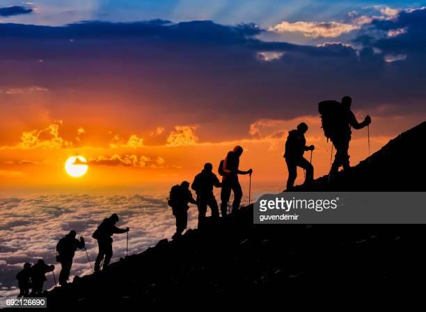 silhouettes of hikers at sunset - alpinismo foto e immagini stock