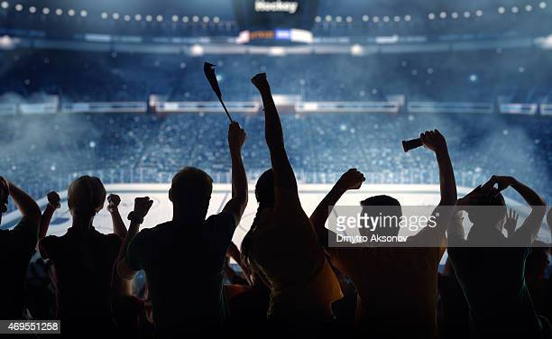 Silhouettes of hockey fans at a hockey game