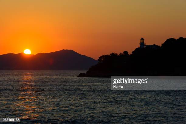 Silhouettes of islands and lighthouse at sunset, Hong Kong