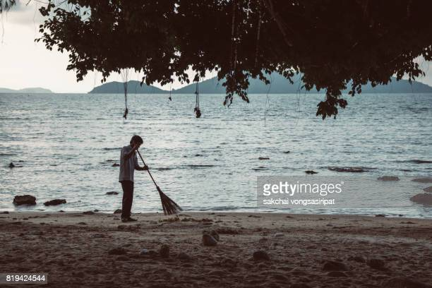 Silhouettes Of Man Sweeping On The Beach