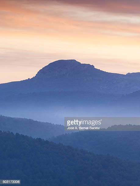 Silhouettes of mountains at sunrise with mist