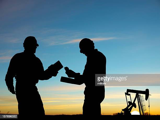 2 silhouettes of oil workers and a pump